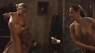 Topless mistress whips a slave while the other rubs her wet pussy